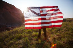 American Patriot in Nature. Young unrecognizable man standing in hills of mountainside spreading big USA banner holding it high in raised arms lit by sunlight Royalty Free Stock Photo