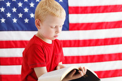 American patriotic boy reading Holy Bible Stock Photos