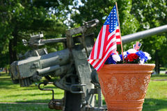 American Patriotism - Flag and Gun. Red, white and blue carnation decoration with American flags in front of a large, soft-focus deck gun monument stock images