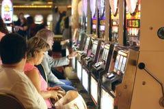 American people play slot machine, Las Vegas. LAS VEGAS, USA - SEPTEMBER 03, 2006: Unidentified gambler American Woman and men playing slot machine in Vegas Royalty Free Stock Images