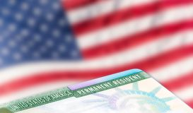 American permanent resident card, immigration concept. United States of America permanent resident card, green card, with US flag in the background. Legal Royalty Free Stock Photography