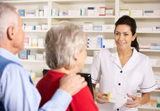 American pharmacist dispensing to senior couple royalty free stock image