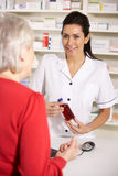 American pharmacist dispensing to senior woman Royalty Free Stock Photography
