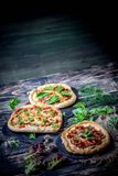 American pizza with mozzarella, tomato, pepperoni on dark wooden table. Sliced pepperoni pizza topping. American pizza on wooden board and various ingredients royalty free stock photo