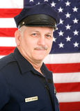 American Policeman. Handsome mature policeman in uniform, against an American Flag Stock Photos