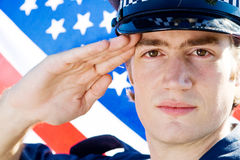 American policeman. Young american policeman saluting, background is USA flag stock images