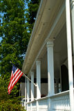 American porch. American flag flying from pillared porch in old new england Stock Photos