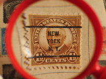 American post stamp  - New York. An old postage stamp featuring president Harding with a New York post office stamp over his face - under a magnifying glass Royalty Free Stock Photography