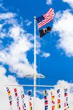 American and POW flags waving. American,  POW  and colorful marine signal flags wave on pole at the central mall at Jones Beach State Park, Long Island New York stock image