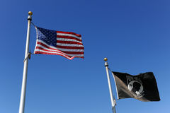 American and POW/MIA Flags. The United States of American flag flies next to black POW/MIA flag over blue sky stock images