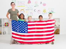 American preschool. Portrait of a happy american preschool students and teacher holding USA flag in classroom royalty free stock photography