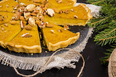 American pumpkin pie. Decorated with assorted nuts on a black background Stock Photo