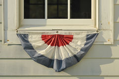 American red white and blue apron flag hanging at the west quodd. Red White and Blue apron flag banner on an old vintage window ledge Royalty Free Stock Images