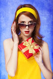 American redhead girl in sunglasses with gift. Photo in 60s style. 2 Royalty Free Stock Image