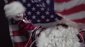 American santa claus fan celebrates holding the flag of USA. The concept of Christmas or Independence Day USA. 4k stock video