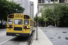 American  school bus horizontal. A school bus parked in a street, waiting the end of the class with the front door open, in dull weather. Back view Stock Photos