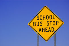 American school bus stop sign. Close up of yellow American road sign with blue sky background saying, school bus stop ahead Royalty Free Stock Photo