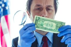 American secret service agent analyzing suspicious counterfeit dollar bill. Conceptual image with selective focus royalty free stock images