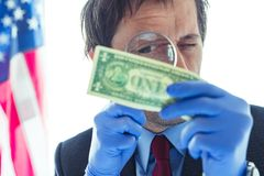 American secret service agent analyzing suspicious counterfeit dollar bill. Conceptual image with selective focus royalty free stock photo