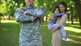 American serviceman in military uniform with wife and son behind, family defense stock footage