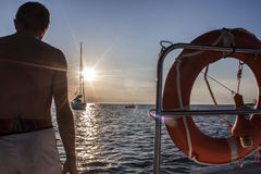 American shot rear view of a man enjoying sunset from a sailing. Boat in the sea. Formentera Spain royalty free stock photos