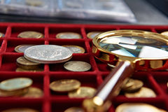 American silver dollar and magnifying glass. On box with coins stock image
