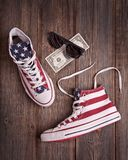 American sneakers, black sunglasses and one dollar on a wooden b royalty free stock photos