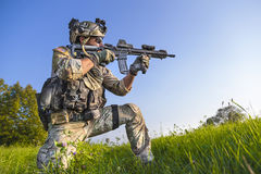 American Soldier aiming his rifle on blue sky background. Portrait of American Soldier aiming his rifle on blue sky background Stock Images
