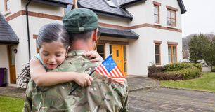 American soldier carrying girl in front of a house Royalty Free Stock Photography