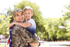 American soldier with her son outdoors. Military service. American soldier hugging with her son outdoors. Military service royalty free stock photo