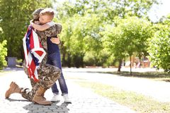 American soldier with her son outdoors. Military service. American soldier hugging with her son outdoors. Military service stock photo