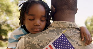American soldier is hugging his son. In a park stock video