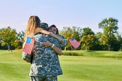 American soldier reunited with his family in park. royalty free stock photo