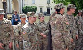 American soldier in uniform and civil man in suit shaking hands royalty free stock photo