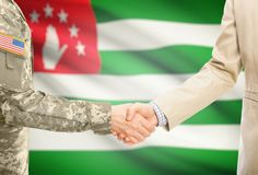 USA military man in uniform and civil man in suit shaking hands with adequate national flag on background - Abkhazia. American soldier in uniform and civil men Royalty Free Stock Images