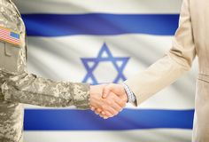 USA military man in uniform and civil man in suit shaking hands with adequate national flag on background - Israel. American soldier in uniform and civil men in Royalty Free Stock Photo