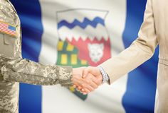 USA military man in uniform and civil man in suit shaking hands with certain Canadian province flag on background - Northwest Terr Stock Photos