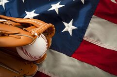 American sports and college athletics concept with the USA flag in the background and macro on a vintage baseball glove holding a