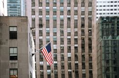 American Stars and Stripes Flag Against Building Facades stock images