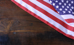 American Stars and Stripes Flag on Rustic Wood Background. USA American stars and stripes flag on dark reclaimed wood background with copy space royalty free stock images