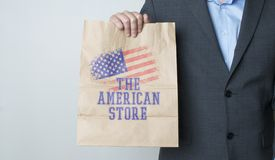 The american store. Manin a suit holding a paper bag Stock Photos