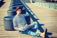 American student studying in New York. Wearing fashionable long sleeve striped T shirt, jeans, boots, sitting on wooden floor, stretching legs, working on Stock Image