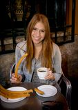 American student tourist girl sitting having spanish typical hot chocolate with churros smiling happy Royalty Free Stock Image