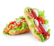 American style hot dog with lettuce, onion and tomato close-up on white background. Fast food. Royalty Free Stock Image
