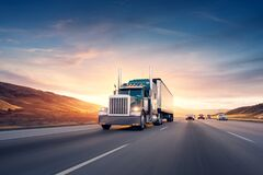 American style truck on freeway pulling load. Transportation theme. Road cars theme