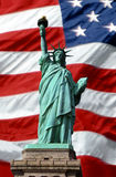 American Symbols of Freedom. Statue of Liberty superimposed over waving American flag royalty free stock photos