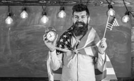 American teacher with american flags holds alarm clock. Man with beard on cheerful face holds flag of USA and clock royalty free stock image