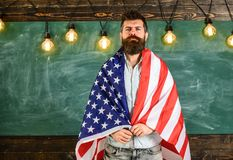 American teacher covered with american flag. Man with beard and mustache on serious face with flag of USA, chalkboard on. Background. Patriotic education Stock Image