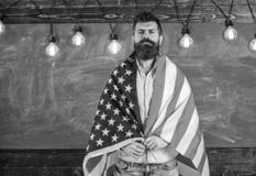 American teacher covered with american flag. Man with beard and mustache on serious face with flag of USA, chalkboard on royalty free stock photo