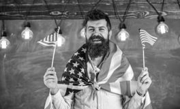 American teacher waves with american flags. Patriotic education concept. Student exchange program. Man with beard and. Mustache on happy face holds flags of USA stock photos